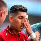 Liverpool's Roberto Firmino receives medical attention during the Premier League match at Wembley
