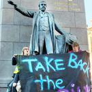 Making a stand: Protesters climb the Parnell statue during a 'Take Back the City' rally last week Photo: Tony Gavin