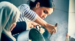 Britain's Meghan, Duchess of Sussex, cooks with women in the Hubb Community Kitchen at the Al Manaar Muslim Cultural Heritage Centre in the aftermath of the Grenfell Tower fire, which has resulted in the publications of 'Together: Our Community Cookbook' and features the women's own personal recipes from across Europe, the Middle East, North Africa and the Eastern Mediterranean and for which the Duchess has written the foreword. Photo: Reuters