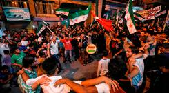 Defiant: Syrians in Idlib, left, dance and chant against the Assad regime. Photo: Getty Images