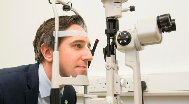 Testing times: Minister for Health Simon Harris looks into a slit lamp during the official opening of the Grangegorman Primary Care Centre in Dublin yesterday. Photo: Gareth Chaney