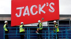 Sign of the times: Workers unveil the branding at Tesco's new discount supermarket Jack's in Chatteris, England. Photo: REUTERS/Chris Radburn