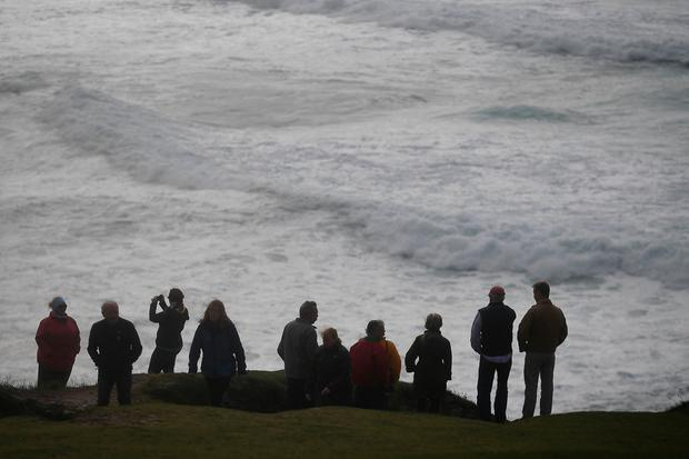 People look out at the sea from Slea Head during Storm Ali in Coumeenoole, Ireland. REUTERS/Clodagh Kilcoyne