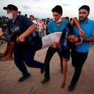 Obstacles: A wounded Palestinian is evacuated during a protest in the northern Gaza Strip calling for lifting the Israeli blockade on Gaza. Photo: REUTERS/Mohammed Salem