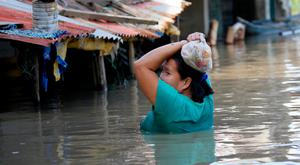 A resident wades through floodwaters after buying basic food items for dinner following flooding brought about by Typhoon Mangkhut which barreled into northeastern Philippines during the weekend and inundated low-lying areas in its 900-kilometer wide cloud band Monday (AP Photo/Bullit Marquez)