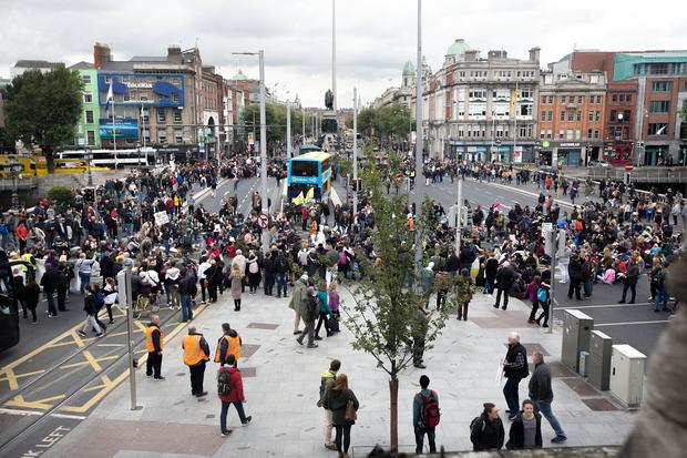 FINDING VOICE: Passersby and protestors on O'Connell Bridge in Dublin yesterday where a Take Back The City group organised a demonstration. Photo: Tony Gavin