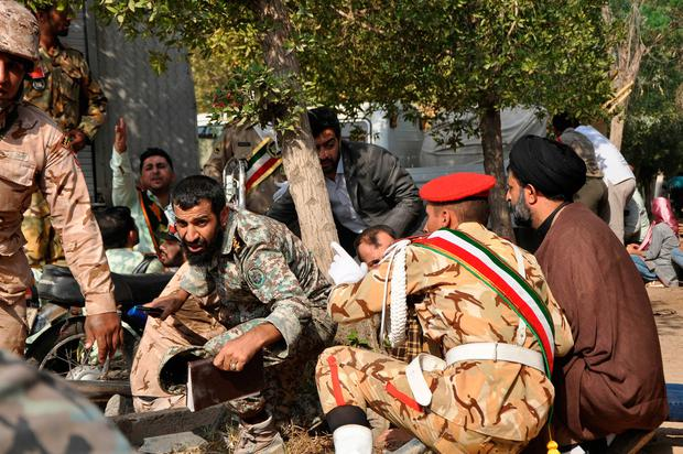 In this photo provided by the Iranian Students' News Agency, ISNA, Iranian armed forces members and civilians take shelter in a shooting during a military parade marking the 38th anniversary of Iraq's 1980 invasion of Iran, in the southwestern city of Ahvaz, Iran, Saturday, Sept. 22, 2018. (AP Photo/ISNA, Behrad Ghasemi)
