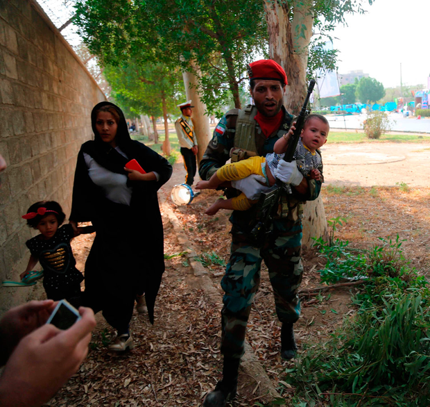 Evacuation: An Iranian soldier carries away a child at the site of an attack on a military parade in the southwestern Iranian city of Ahva. Photo: Getty Images