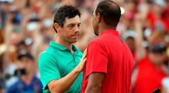 Tiger Woods shakes hands with Rory McIlroy after winning the Tour Championship golf tournament at East Lake