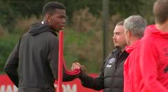 Strained relations: Paul Pogba reacts to something Jose Mourinho said at training yesterday
