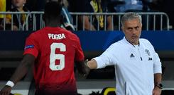 Manchester United's Paul Pogba (L) shakes hands with Jose Mourinho after being substituted