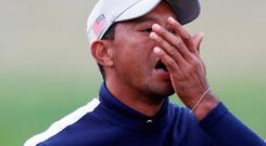 Tiger Woods swallows something during day one