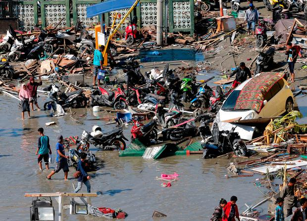 People survey damage outside the shopping mall following earthquakes and tsunami in Palu, Central Sulawesi, Indonesia