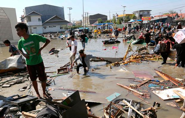People survey the damage of the shopping mall following earthquakes and a tsunami in Palu, Central Sulawesi, Indonesia