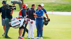 Rory McIlroy of Europe shakes hands with Justin Thomas of the United States on the 18th fairway