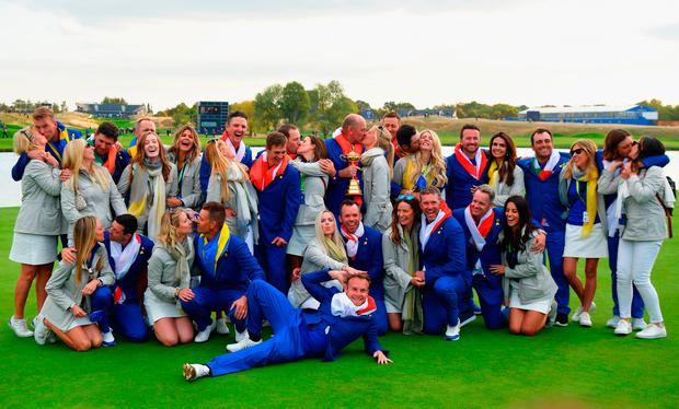 Sealed with a kiss: Team Europe kiss their partners as they celebrate winning the Ryder Cup at Le Golf National in Paris. Photo: Stuart Franklin/Getty Images