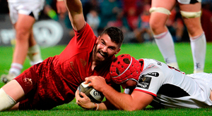 Sammy Arnold of Munster celebrates after scoring his side's seventh try despite the tackle of Ulster's Eric O'Sullivan during Saturday night's PRO14 clash at Thomond Park. Photo: Matt Browne/Sportsfile