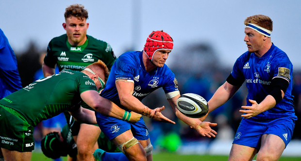 Leinster's Josh van der Flier offloads to team-mate James Tracy as he is tackled by Sean O'Brien of Connacht. Photo: Brendan Moran/Sportsfile