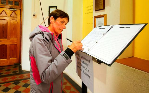 Sympathy: Hanna O'Leary signs the book of condolence for the men who drowned, in the church in Cahersiveen, Co Kerry. Photo: Gerry Mooney