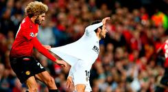 Valencia's Daniel Parejo has his shirt pulled back by Manchester United's Marouane Fellaini at Old Trafford last night. Photo: Clive Brunskill/Getty Images