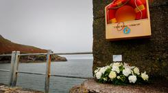 Flowers are left on the harbour wall in Coonanna for the three men who drowned on Sunday evening. Photo: Gerry Mooney