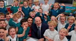 All smiles: Seán Gallagher at St Laurence's Primary School, Greystones, with his wife Trish and their son Bobby (5) and pupils from his class. Picture: Collins