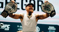 Conor McGregor holds up belts during a news conference for the UFC 229