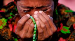 A woman cries as she attends a mass prayer for Palu at Talise beach in Palu, Indonesia. Photo: Reuters