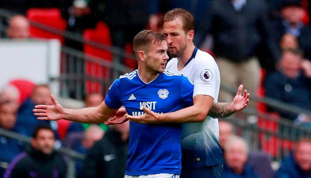 Cardiff City's Joe Ralls is escorted off the pitch by Tottenham's Harry Kane after being shown a red card by referee Mike Dean