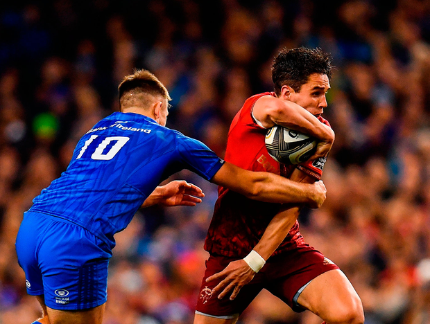 Joey Carbery of Munster is tackled by Ross Byrne of Leinster. Photo: Seb Daly/Sportsfile