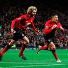 Maroune Fellaini rushes to join in as Alexis Sanchez tunrs away in celebration after scoring the winner for Manchester United at Old Trafford. Photo: Martin Rickett/PA