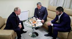 Russian President Vladimir Putin (L) meets with mixed martial arts fighter Khabib Nurmagomedov of Russia (R), UFC lightweight champion who recently defeated Conor McGregor of Ireland in the main event of UFC 229, and his father Abdulmanap Nurmagomedov on the sidelines of a sports forum in Ulyanovsk, Russia