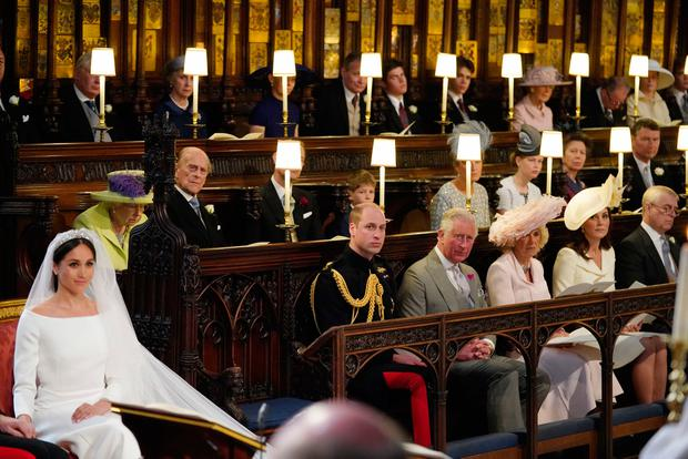 Meghan Markle (L) in St George's Chapel, Windsor Castle for her wedding to Britain's Prince Harry, Duke of Sussex, watched by (middle row L-R) Britain's Queen Elizabeth II, Britain's Prince Philip, Duke of Edinburgh, Britain's Prince Edward, Earl of Wessex, Page boy James, Viscount Severn, Britain's Sophie, Countess of Wessex, Britain's Lady Louise Windsor, Britain's Princess Anne, Princess Royal, Vice Admiral Timothy Laurence, (front row L-R) Britain's Prince William, Duke of Cambridge, Britain's Prince Charles, Prince of Wales, Britain's Camilla, Duchess of Cornwall, Duchess of Britain's Catherine, Duchess of Cambridge, and Britain's Prince Andrew, Duke of York