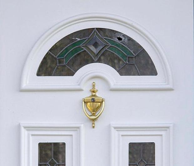 A bullet hole in the front door of the house after the incident