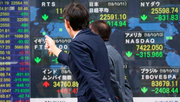 People look at an electronic stock board of a securities firm in Tokyo. Asian markets tumbled on Thursday, after Wall Street slumped on a heavy selling of technology and internet stocks. Photo: AP