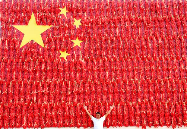 A man poses in front of a giant Chinese flag decorated with red chili peppers in Henan province. Photo: Reuters