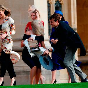 A guest stoops to collect her hat that blew off in the wind as she arrives to attend the wedding of Britain's Princess Eugenie of York to Jack Brooksbank at St George's Chapel, Windsor Castle, in Windsor, on October 12, 2018. (Photo by Adrian DENNIS / various sources / AFP)ADRIAN DENNIS/AFP/Getty Images
