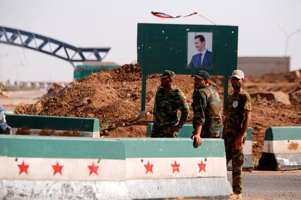 Under guard: Syrian soldiers stand at the Nasib border crossing with Jordan in Deraa, Syria. Photo: Reuters