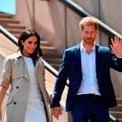 Britain's Prince Harry and his wife Meghan walk down the stairs of Sydneys iconic Opera House to meet people in Sydney on October 16, 2018