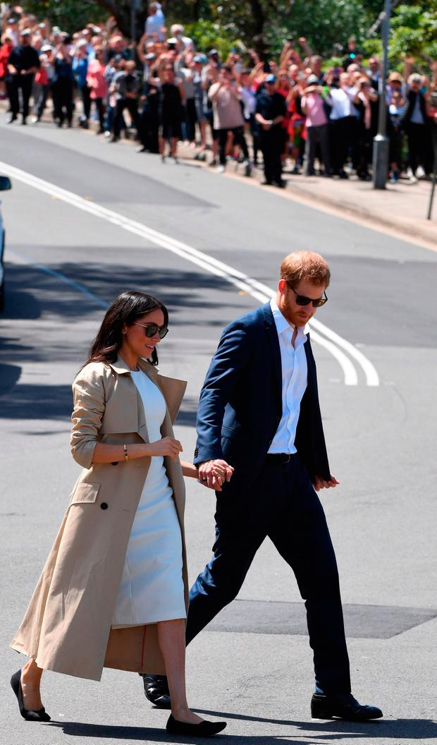 Britain's Prince Harry (R) and his wife Meghan (L) walk to their boat after a visit to Taronga Zoo in Sydney on October 16, 2018