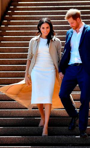 Britain's Prince Harry and his wife Meghan walk down the stairs of the iconic Opera House to meet people on October 16, 2018