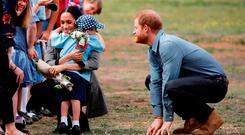 Prince Harry, Duke of Sussex and Meghan, Duchess of Sussex interact with Luke Vincent, 5 after arriving at Dubbo Airport on October 17, 2018 in Dubbo, Australia