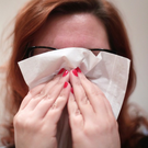 A woman with a cold blowing her nose with a tissue (Yui Mok/PA)