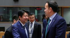 Taoiseach Leo Varadkar greets Japan's Prime Minister Shinzo Abe as they attend the ASEM leaders summit in Brussels yesterday. PHOTO: YVES HERMAN
