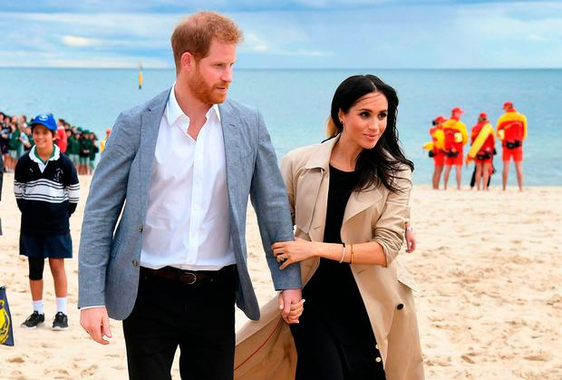 Britain's Prince Harry and his wife Meghan, Duchess of Sussex walk on South Melbourne Beach where they met community groups in Melbourne on October 18, 2018