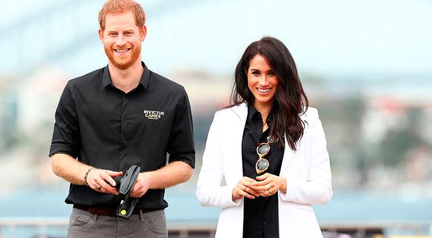Prince Harry, Duke of Sussex and Meghan, Duchess of Sussex watch children control remote control cars during the JLR Drive Day at Cockatoo Island on October 20, 2018 in Sydney, Australia. (Photo by Mark Metcalfe/Getty Images for the Invictus Games Foundation)