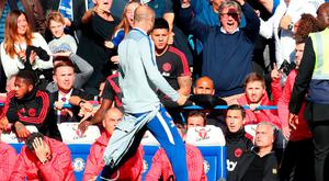 A member of the backroom staff at Chelsea celebrates his sides second goal in front of Jose Mourinho