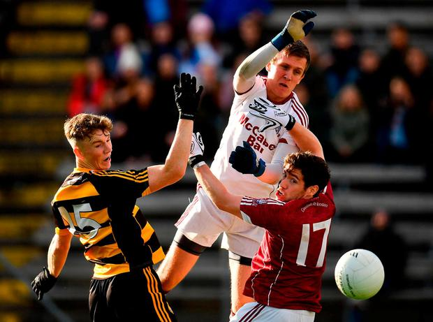 Jamie Leahy, centre, and Enda OConnell of Castlerahan, right, manage to stop Crosserlough's Kieran Galligan. Photo: Seb Daly/Sportsfile