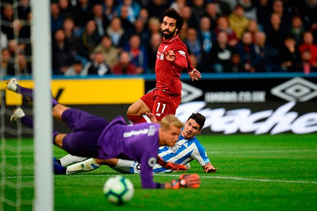 Clincher: Liverpool striker Mohamed Salah shoots past Huddersfield defender Christopher Schindler and goalkeeper Jonas Lossl to score the only goal of Saturday's Premier League clash. Photo: Getty Images