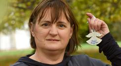 Kathleen Chada holds an angel with the names of her two sons Eoghan and Ruairi before leading a symbolic walk with friends and family members of murder victims in the Phoenix Park at the weekend. Photograph Moya Nolan